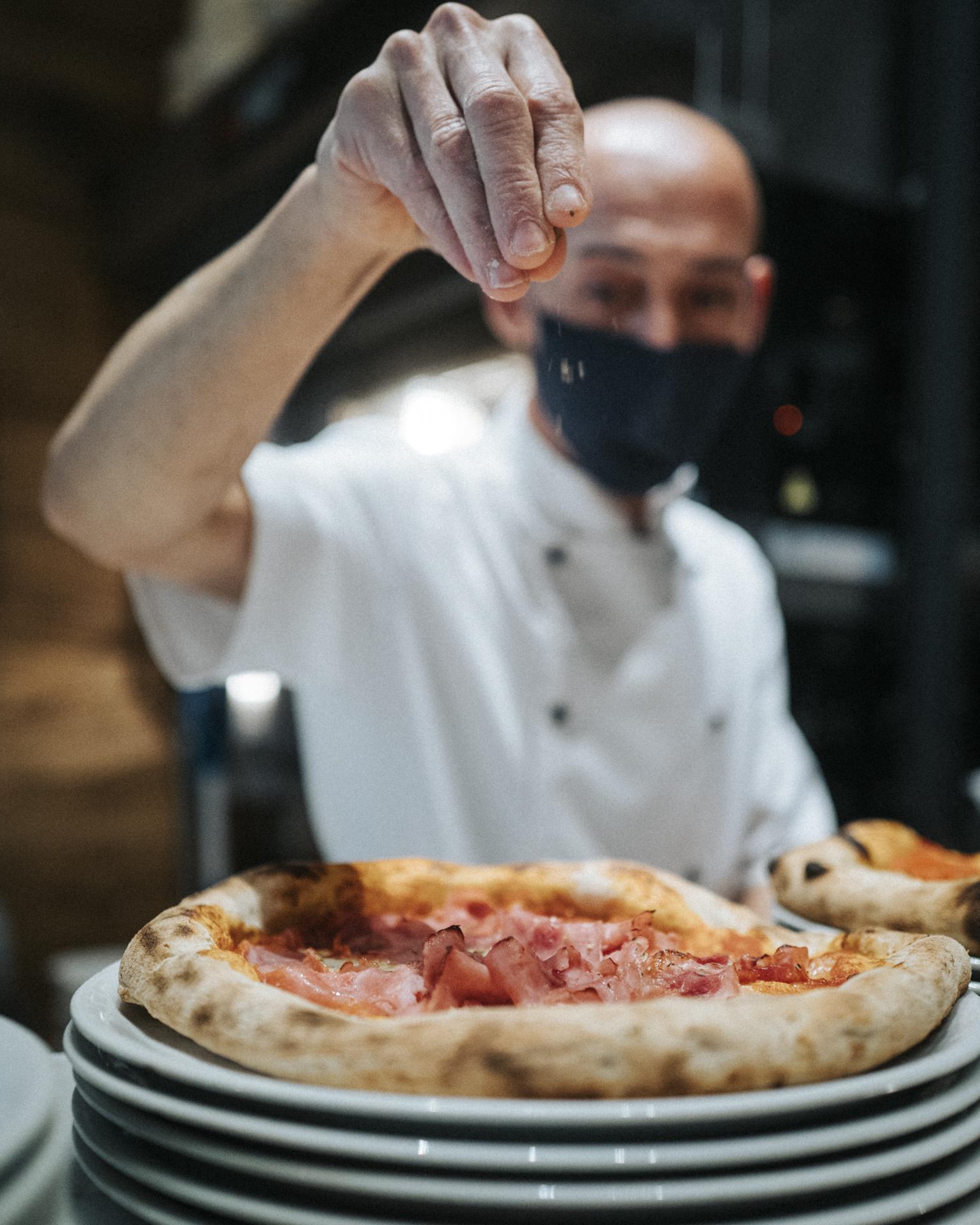 Pizza wird gesalzen