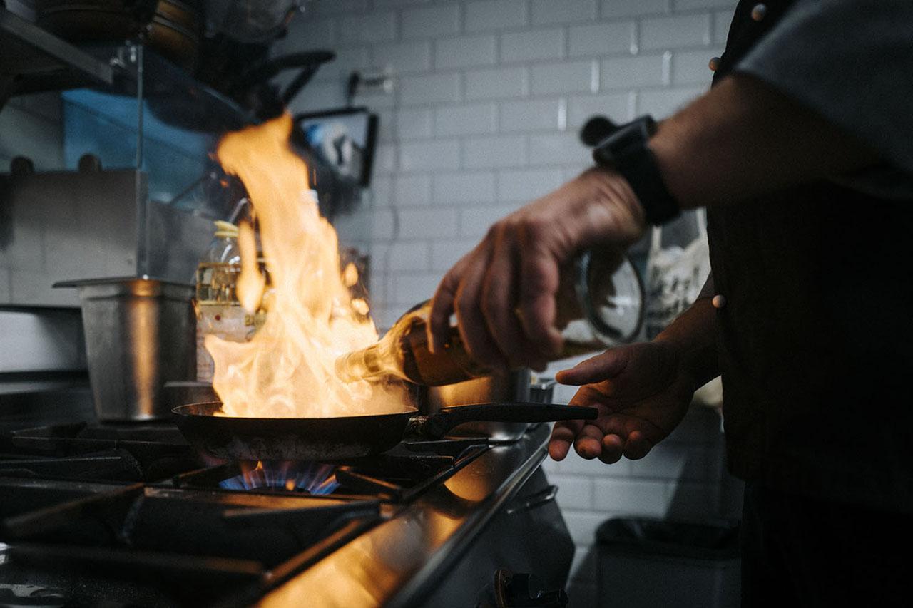 Bei uns ist kochen noch handwerk, hier Pfanne mit Stichflamme