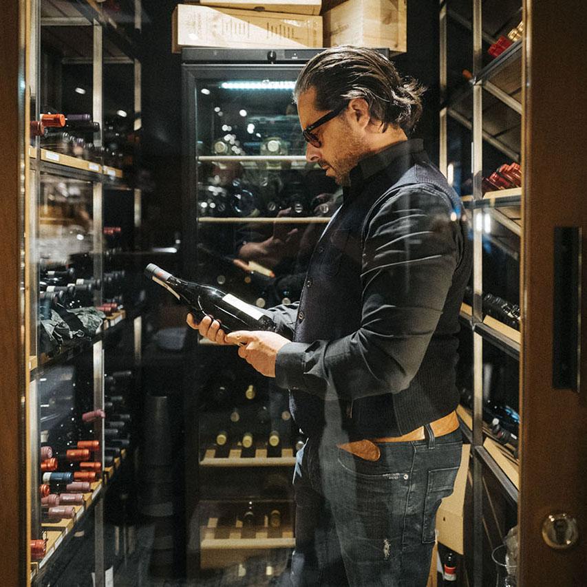 Ignazio Galletto sucht perfekten Wein aus dem Weinschrank aus.